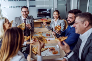 group-business-people-sitting-boardroom-chatting-laughing-having-pizza-lunch_232070-6432
