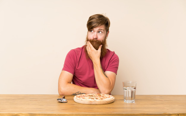 redhead-man-with-long-beard-table-with-pizza-thinking-idea_1368-43478